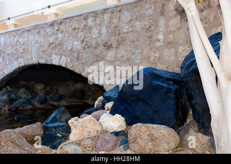 Black and brown rocks and stones lying near small arch bridge in the garden or park - Stock Photo