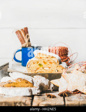 Traditional German Christmas cake Stollen with gingerbread cookies, white background - Stock Photo