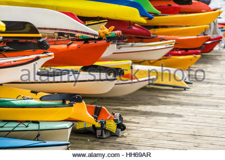 Colorful canoes and kayaks by the lake on a sunny day. Used for summer boating and recreational sport activities - Stock Photo