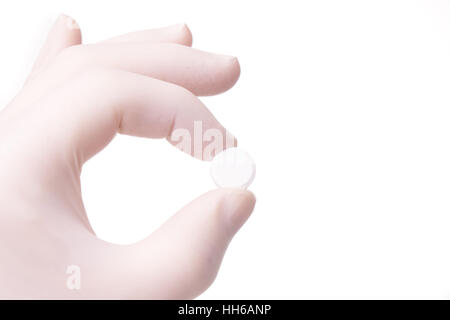 gloved hand holding small round pill. Hand and medicines are isolated on white background - Stock Photo
