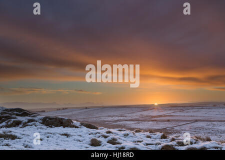 A dramatic winter sunrise on a snowy day beside the Hadrian's Wall Path, close to Caw Gap and Bogle Hole - Stock Photo