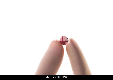 Gloved hand holding red tablet in between thumb and finger on white background - Stock Photo