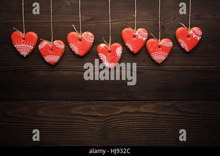 Close up of line of red gingerbreads hearts on ribbon. Festive cookies decorated with sweet sugar mastic for Valentines - Stock Photo