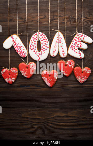Reflection effect of line of sweet gingerbreads hearts and world Love on wooden background. Creative idea for decoration - Stock Photo