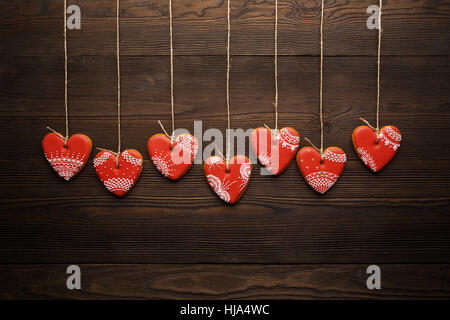 Line of red gingerbreads hearts on ribbon. - Stock Photo