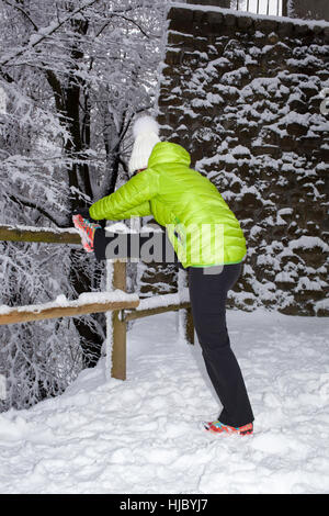 Mid aged woman doing stretching in winter city park - Stock Photo
