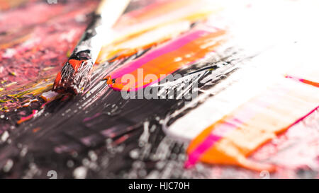 paint brush on wet acrylic paint with several colors - Stock Photo