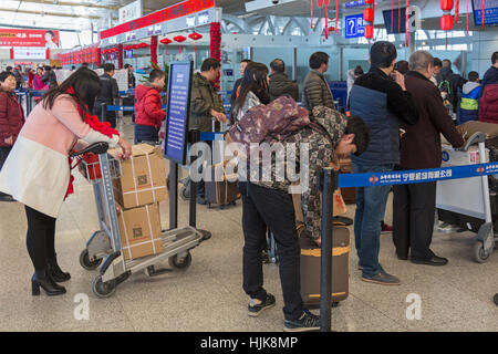 Passengers at check-in desk at Yinchuan Hedong International Airport, Ningxia province,,China - Stock Photo