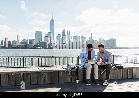 USA, two businessmen working at New Jersey waterfront with view to Manhattan - Stock Photo