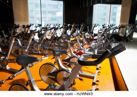 Aerobics spinning exercise bikes gym room with many in a row - Stockfoto