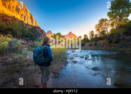 Backpacker exploring Zion National Park near the virgin river - Stock Photo