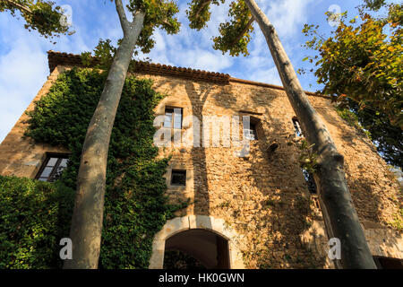 Gala Dali Castle Museum facade amidst tall trees, medieval home of Salvador Dali, Pubol, Baix Emporda, Girona, Catalonia, - Stock Photo