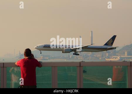 A Planespotter is taking photo of Singapore Airlines Boeing 777-300ER 9V-SWF landing at Hong Kong International - Stock Photo