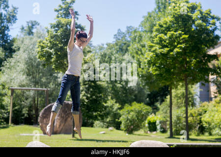 Mature woman jumping on rock in the park, Freiburg im Breisgau, Baden-Württemberg, Germany - Stock Photo
