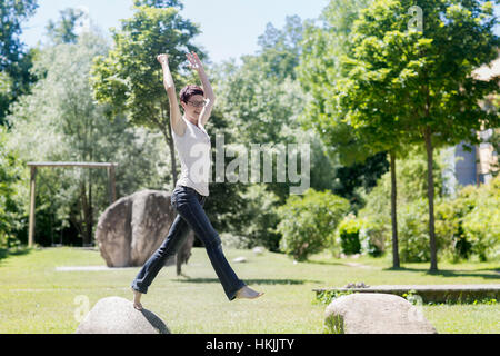Mature woman jumping from one rock to another rock in the park, Freiburg im Breisgau, Baden-Württemberg, Germany - Stock Photo