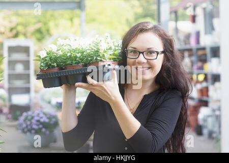 Happy young woman working in garden,Freiburg im Breisgau,Baden-Württemberg,Germany - Stock Photo