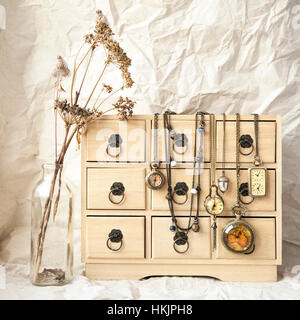 Some old vintage pocket watches on a wooden jewelry storage box, time concept. Retro still life - dry wild flowers - Stock Photo