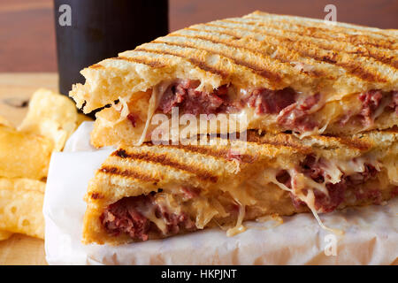 A hot grilled panini sandwich with meat and melting cheese. The sandwich is cut and stacked in front of a beer bottle - Stockfoto