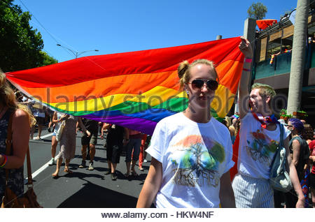 Melbourne, Australia. 29th Jan, 2017. People march holding a rainbow flag as over 40,000 come together on the streets - Stock Photo