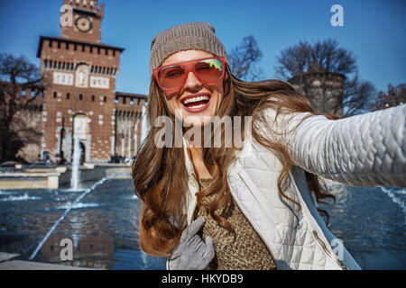 Rediscovering things everybody love in Milan. happy young woman near Sforza Castle in Milan, Italy taking selfie - Stock Photo