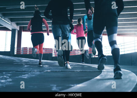 Back view of sportsmen running in a group outdoors over urban background. Copyspace. - Stockfoto