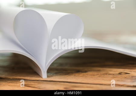 Book with opened pages of shape of heart - Stock Photo