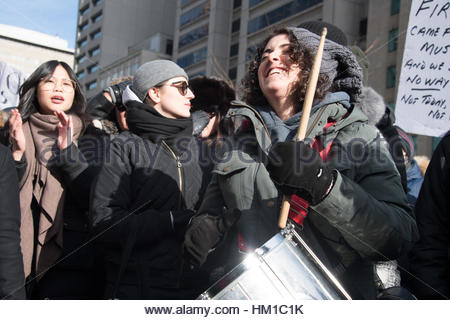 Toronto, Canada. 30th Jan, 2017. Girl musician protesting among a crowd. Multicultural demonstrators hold an anti - Stock Photo