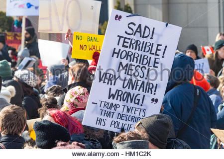 Toronto, Canada. 30th Jan, 2017. Close shot of crowd and an anti-Trump sign. Multicultural demonstrators hold an - Stock Photo