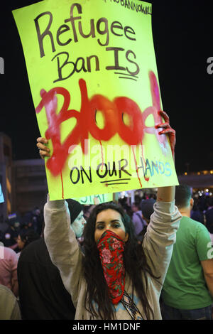 Los Angeles, USA. 29th Jan, 2017. A woman holds a sign reading ''Refugee Ban Is Blood On Our Hands'' as people protest - Stock Photo