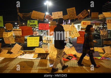Los Angeles, USA. 29th Jan, 2017. Signs decorate a parking lot fence on the edge of the airport after protests at - Stock Photo