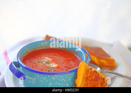 Tomato soup in a blue bowl with a grilled cheese sandwich cut in triangles and room for text - Stock Photo