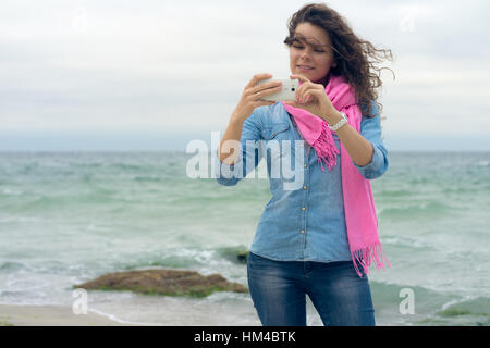 Young smiling woman with curly hair in a denim shirt makes the photo self on smartphone. Happy weekend on the coast. - Stockfoto