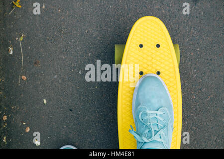 Female feet in blue sneakers on a yellow skateboard with green wheels riding on the road, top view - Stock Photo