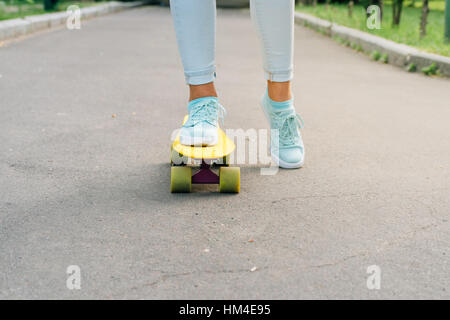 Female feet in sneakers riding a skateboard on asphalt - Stock Photo