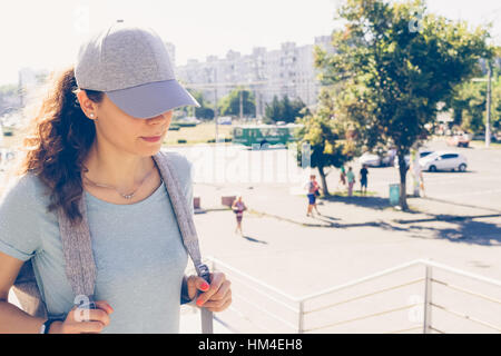 Young woman in cap and a backpack walks up the stairs on the background of summer city, yellow toning - Stock Photo
