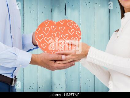 Composite image of couple holding pink heart against blue wooden panels - Stock Photo