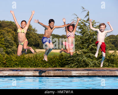 Group Of Children Jumping Into Outdoor Swimming Pool - Stock Photo