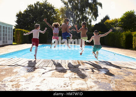 Rear View Of Children Jumping Into Outdoor Swimming Pool - Stock Photo