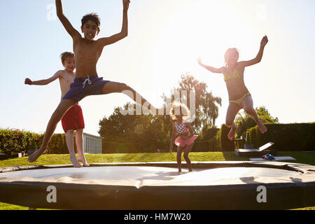 Group Of Children Having Fun Jumping On Outdoor Trampoline - Stock Photo