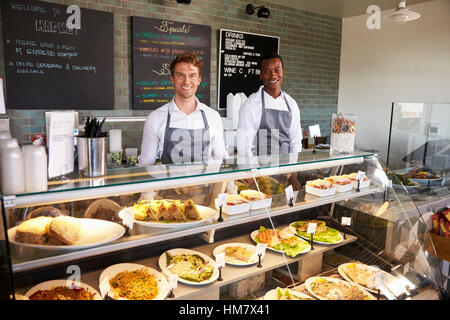 Male Staff Working Behind Counter In Delicatessen - Stock Photo