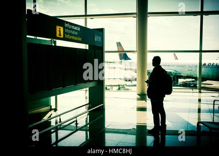 Passenger in Barcelona airport, looking the airplanes through the window, toward the runway, by the information - Stock Photo