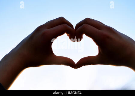 Two hands creating a heart shape against blue sky - Stock Photo
