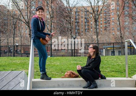 Jersey City, New Jersey, USA. Two female students enjoying their musical instruments. - Stock Photo
