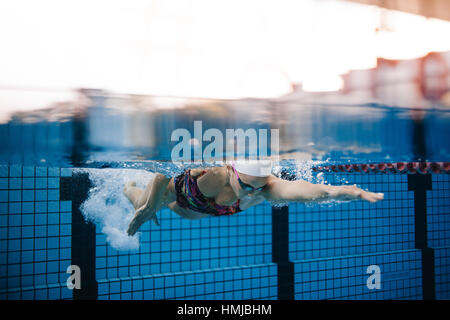 Underwater shot of female swimmer swimming in pool. Fit young female swimmer training in the pool. - Stockfoto