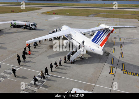 passengers carry-on bags boarding Air France - CityJet BAE 146 Avro RJ-85 parked Air BP Refuelling bowser behind - Stock Photo