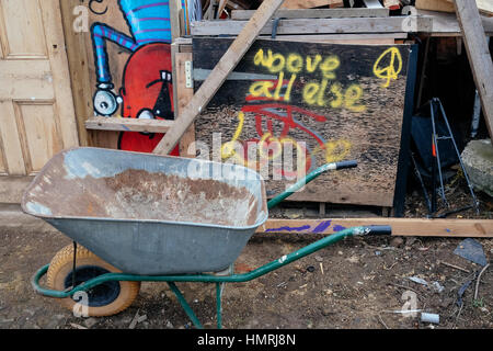 'Above all else Love' graffiti sprayed over the wooden board; garden cart standing by the side - Stock Photo