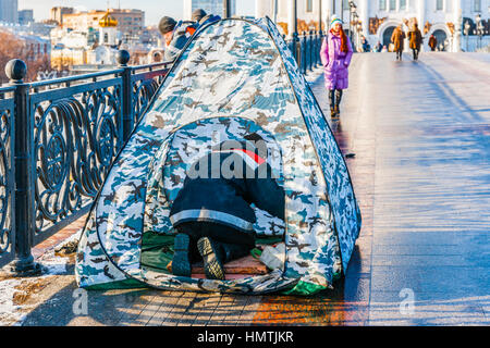 Moscow, Russia. 5th Feb, 2017. Unidentified, unrecognizable worker in protective tent repairs floor illumination - Stock Photo