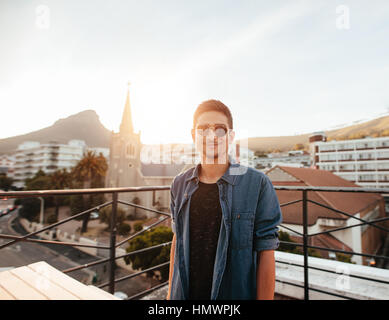 Portrait of handsome young man standing on the rooftop. Caucasian young guy wearing sunglasses on terrace looking - Stock Photo
