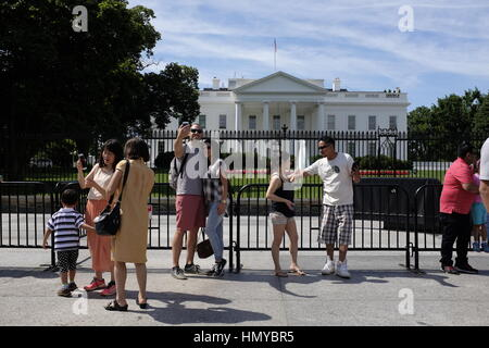 Tourists take selfies in front of The White House. - Stock Photo