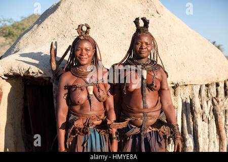 Himba women posing for a photo during a village visit. - Stock Photo